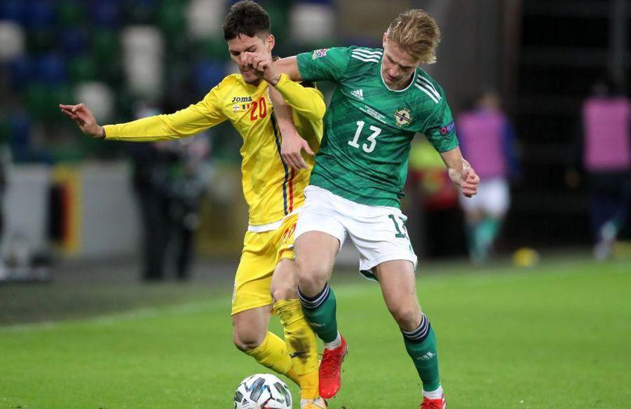 Man se luptă să îi ia fața unui adversar în meciul cu Irlanda de Nord