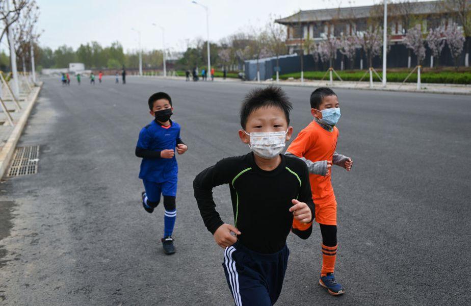Copiii chinezi aleargă cu măști de protecție FOTO: Guliver/GettyImages