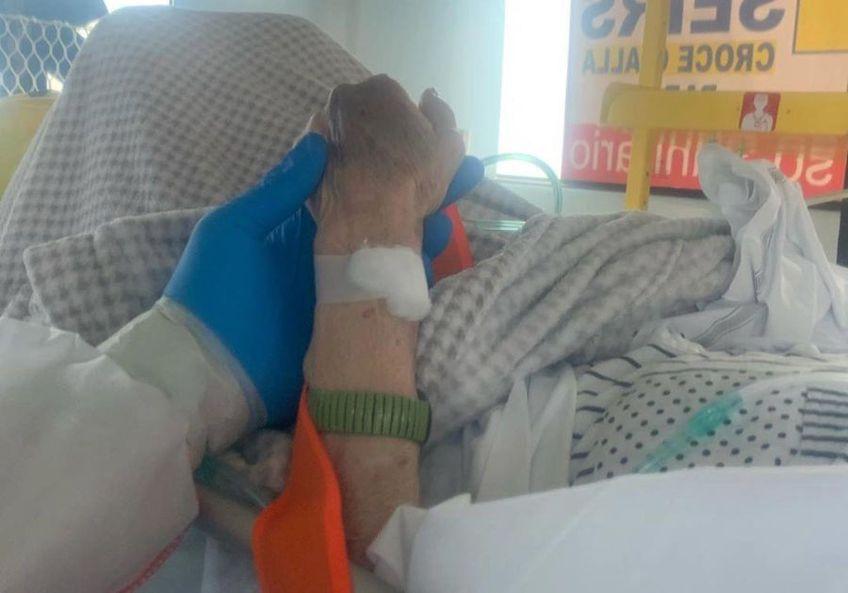 Maxime Mbanda ține de mână o bătrânică în salvarea spre spital.