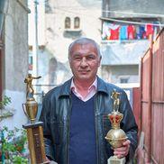 Ilie Dragomir pozând în curtea din Ferentari cu două dintre cele mai dragi cupe ale sale