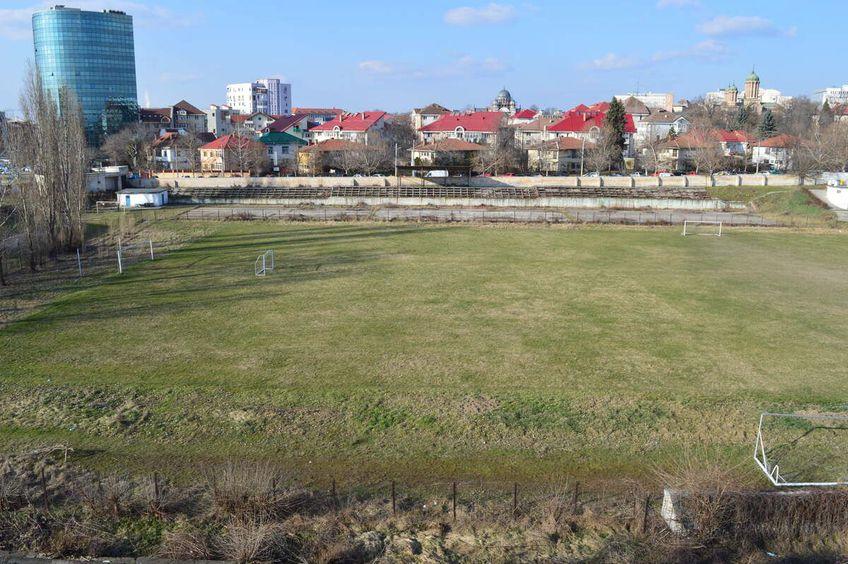 Fostul stadion arată jalnic, pe fundal se zărește noua arenă, cunoscută ca OZN-ul din Bănie
