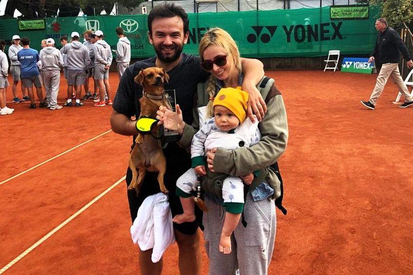 Florin Mergea, soția sa, Daiana, băiețelul lor, Noah, și câinele familiei, sărbătorind cu trofeul de la Meerbusch